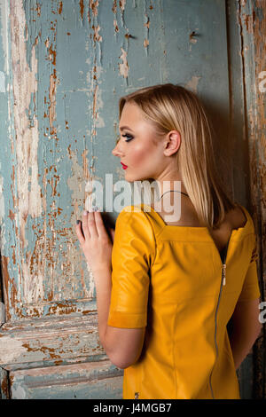 Studio shot of young and beautiful girl in yellow dress wearing in studio. - Stock Image