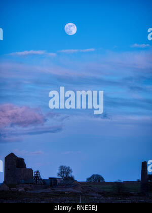 Derbyshire, UK. 18th Feb, 2019. Super Snow Full Moon rising over Magpie Mine historic buildings in the Peak District National Park, Derbyshire. The full moon will reach its closest point to Earth at 9.06 am on Tuesday 19th February 2019. It will be the biggest and brightest of the entire year appearing 14% bigger than usual and 30% brighter. Credit: Doug Blane/Alamy Live News - Stock Image