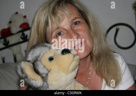 portrait of woman holding cuddly toy dog - Stock Image