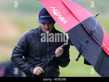 Portrush, County Antrim, Northern Ireland. 17th July 2019. The 148th Open Golf Championship, Royal Portrush Golf Club, Practice day ; Justin Rose (ENG) shelters from the rain under an umbrella on the 14th hole Credit: Action Plus Sports Images/Alamy Live News - Stock Image