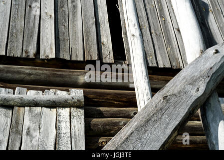 Closeup details of an old log timber home with aged and textured wood. Exterior wooden patterns with daytime sunshine - Stock Image