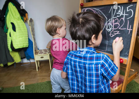 Brothers writing on a blackboard, Munich, Germany - Stock Image