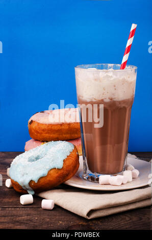 Milkshake and donuts in glass on blue background - Stock Image