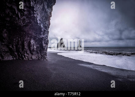 Cold sea water rolling on wet sand near rough stony cliffs on stormy day on Reynisfjara Black Beach in Iceland - Stock Image