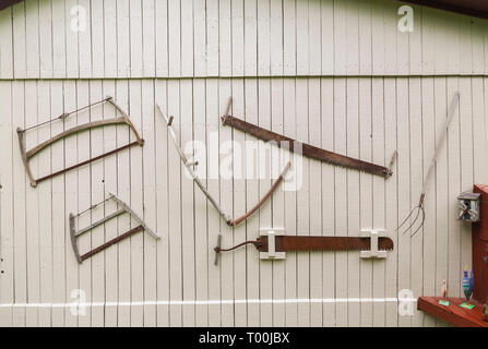 Antique saws, pitchfork and other hand tools hanging on the side wall of old grey painted wooden planked barn in residential backyard - Stock Image