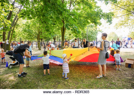 Poznan, Poland - May 27, 2018: Adults, boys and girls standing around a circle shaped colorful cloth on a Kindernalia event at the Jan Pawla II park - Stock Image