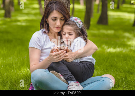 Young mom and little girl look at photos at smart phone after take selfie.Happy mother and daughter moments with love and natural emotion. - Stock Image
