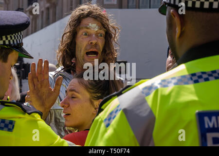 London, UK. 19th April 2019. A man argues with police and tries to go though the police cordon around Extinction Rebellion's Sea of Protest after police surrounded the yacht and put a cordon around the area. They police began the slow process of persuading protesters to leave by threatening them with arrest and cutting off those who were locked on around the bottom of the yacht. There were a number of arrests of protesters who refused to leave. A few tried to get the large crowd to protect the yacht, but XR organisers persuaded them not to physically oppose the police action. Peter Marshall/Al - Stock Image