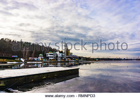 Poznan, Poland - February 10, 2019: Pier by the Malta lake with building in the background on a cloudy day. - Stock Image