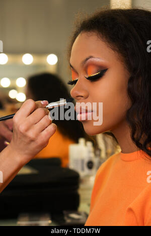 Makeup artist applies foundation for makeup of african girl. Evening make-up. Closeup portrait. - Stock Image