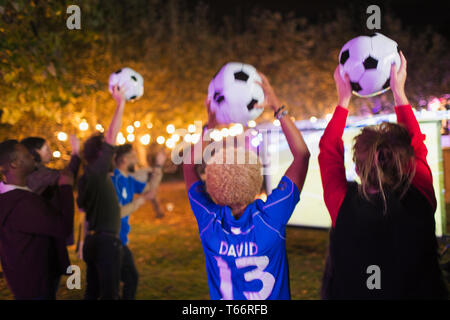 Happy friends with soccer balls cheering, watching soccer match in backyard - Stock Image