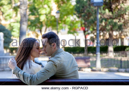 Rear view of a young couple in love flirting on the bench of a public park in daylight - Stock Image