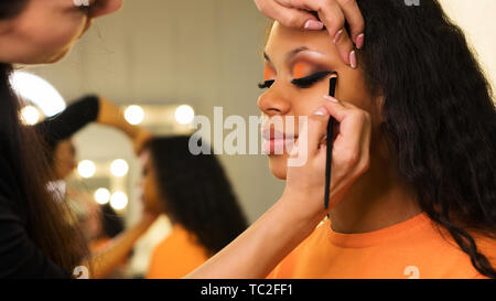 Makeup artist draws arrows on eyelids of african girl. Evening make-up. Closeup portrait side view - Stock Image