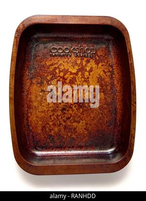 A well used burnt cooking tin - Stock Image