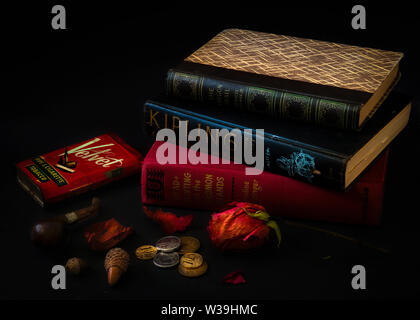Vintage still life with stacked up books and pipe smoking apparatus on black background hardbound, stacked, vintage, classic books closed on a desk wi - Stock Image