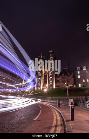 A long exposure of a buss passing by in front of New College, Edinburgh at night - Stock Image