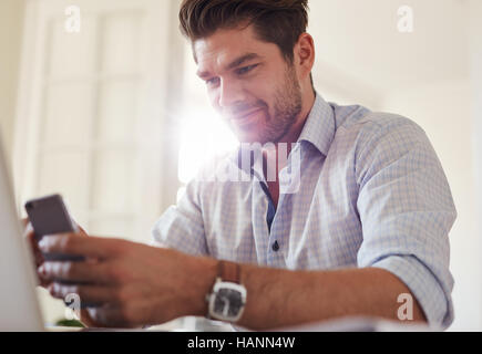 Shot of handsome young man sitting at home using mobile phone. Caucasian business man reading text message on his - Stock Image