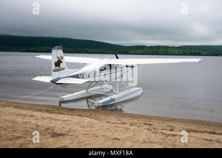 A 1973 Cessna 180J float plane tied up on the sand beach on Lake Pleasant in Speculator, NY USA - Stock Image