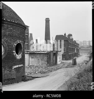 Etruria Pottery Works, Stoke-on-Trent, Staffordshire, 1965-1968. Josiah Wedgwood's Etruria Pottery Works during demolition, viewed from towpath of the Trent and Mersey Canal with the Round House in the foreground. Josiah Wedgwood opened his Etruria Works beside the Trent and Mersey Canal in 1769. A new factory was constructed at Barlaston in 1938 and production was gradually shifted away from Etruria. The Round House (built circa 1769), said to have been used for grinding raw materials, as a counting house, and as a stable, is now the only surviving structure. - Stock Image