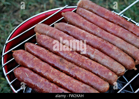 Sausages cooking over a camping grill. - Stock Image