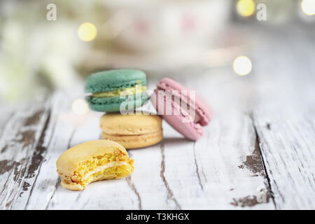 Bite missing from a lemon french macaron in front of a stack of macarons on a white rustic table.. - Stock Image