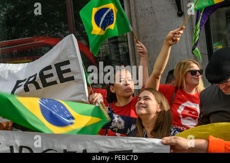 London, UK. 13th August 2018.  Brazilians wave Brazilian flags at the protest outside the Brazilian embassy calling for the release of Luiz Inacio Lula da Silva, a former trade union leader who was President of Brazil from 2003-11 to enable him to stand for election again in October. Credit: Peter Marshall/Alamy Live News - Stock Image