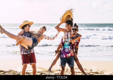 Group of people friends have fun and playing carrying the girls and laughing a lot in friendship - happiness on vacation enjoying the sandy tropical r - Stock Image