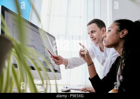 Man and woman discussing data on a large computer screen - Stock Image