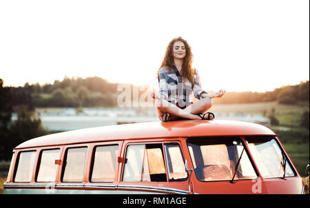 A young girl on a roadtrip through countryside, sitting on the roof of minivan doing yoga. - Stock Image