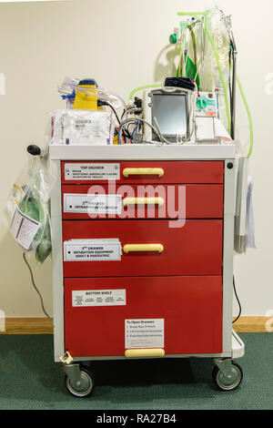 Hospital crash trolley for emergency resuscitation with a electrocardiograph ECG and a defibrillator along with emergency fluids etc. - Stock Image
