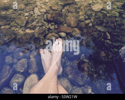 Feet resting in a cold mountain stream, Cleopatra Pools, Abel Tasman National Park, New Zealand - Stock Image