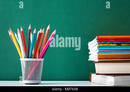 Stack of colorful textbooks and copybooks with pencils near by on background of blackboard - Stock Image