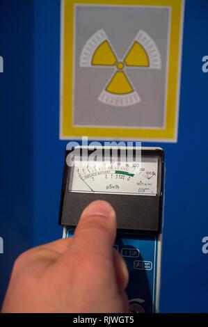 Hand-held radiation survey instrument detecting no radiation. Ionizing radiation hazard symbol as background - Stock Image