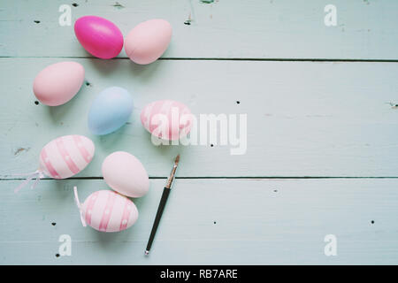 A beautiful and colorful close-up flat of isolated easter eggs in plain colors and striped by a small brush over a pastel blue wooden table with space - Stock Image