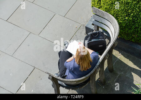 A single woman on a park bench writing on a notepad, - Stock Image