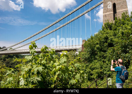 A male trouist taking photograph of The Clifton Suspension Bridge spanning Avon Gorge and River Avon, Bristol, UK - Stock Image