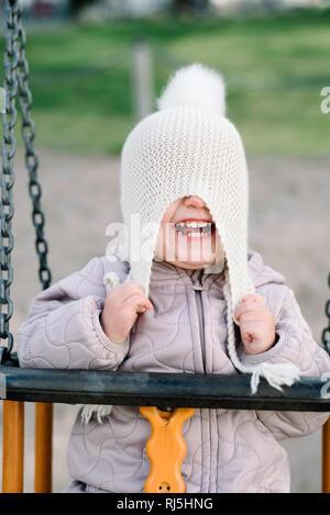 Girl having fun on swing in playground - Stock Image