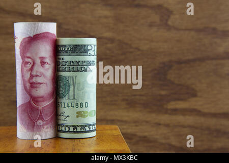 American dollar and Chinese yuan placed together against wood background symbolizes an integrated business environment - Stock Image
