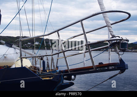 A view of a safety bow rail on a modern, moored sailing vessel showing parts of the rigging - Stock Image