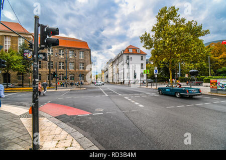 A man drives a convertible vintage car drives through the Mitte district towards Museum Island in the urban center of Berlin, Germany. - Stock Image