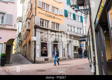 Zurich, Switzerland - March 2017: People walking in posh Glockengasse high street, a small medieval alley with elegant shops in Zurich city centre, Sw - Stock Image