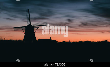 Silhouette of traditional Dutch windmill at sunset at sunset. - Stock Image