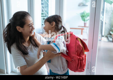 asian mother help her daughter to put the backpack on before going to school - Stock Image