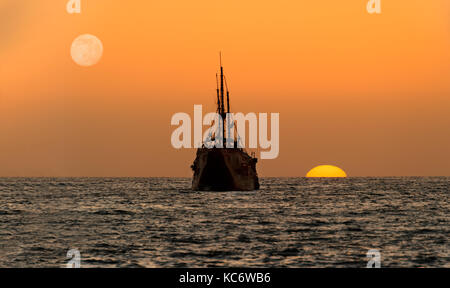Ocean sunset ship silhouette is an old wooden ship sitting at sea watching the sunset on the ocean horizon. - Stock Image