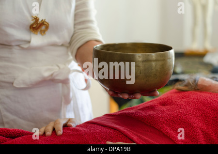 Practitioner healing with Tibetan singing bowls - Stock Image