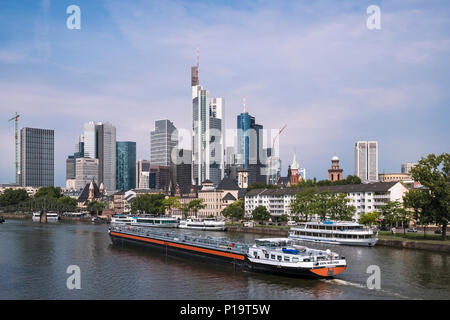A large barge travels on the river Main, past the citys modern architecture skyscraper skyline, Frankfurt am Main, Hesse, Germany - Stock Image