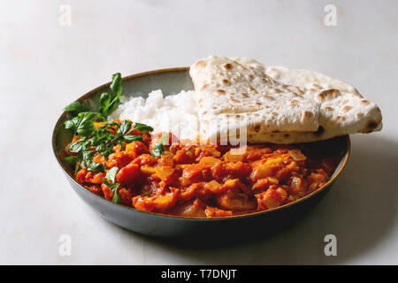 Vegan vegetarian curry with ripe yellow jackfruit served in ceramic bowl with rice, coriander and homemade flatbread flapjack over white marble table. - Stock Image