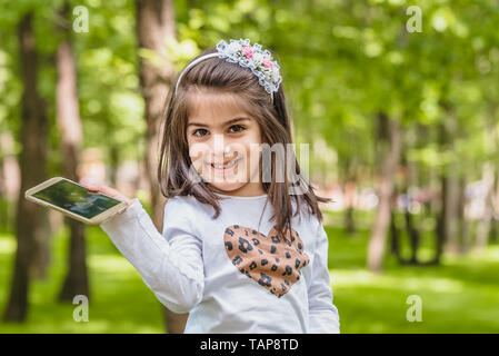 Adorable four years old cute little girl in casual clothes holds mobile phone, looking at camera and smiling lifestyle outdoor in park - Stock Image