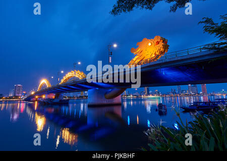 Dragon Bridge at night in Da Nang, Vietnam. The dragon's head spews out flames and sprays of water every weekend, and is a landmark to the city. - Stock Image