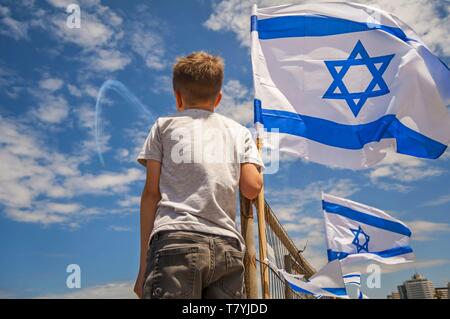 Israeli kid watching the aviation show on the 71 Israel Independence Day with a flag of Israel against the blue sky. - Stock Image